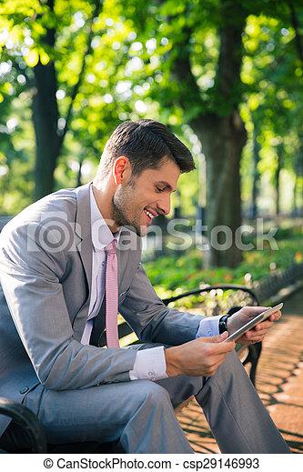 Businessman using tablet computer outdoors - csp29146993