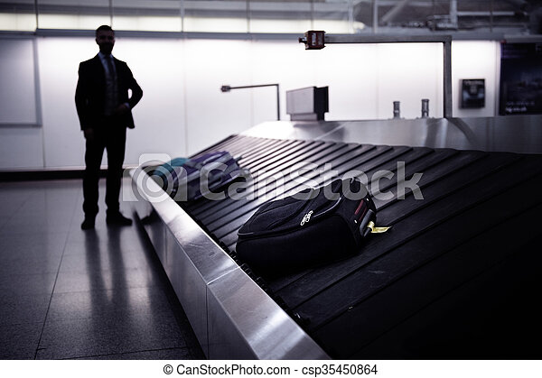 Businessman waiting for suitcase on luggage conveyor belt, airport - csp35450864