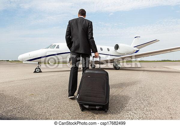 Businessman Walking Towards Corporate Jet - csp17682499