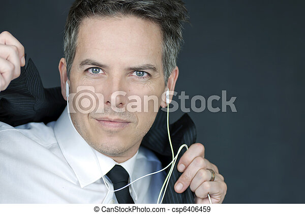 Businessman Wearing Headphones Puts On Suit Jacket - csp6406459