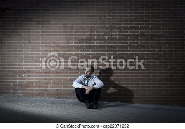businessman who lost job lost in depression sitting on city street corner - csp22071232