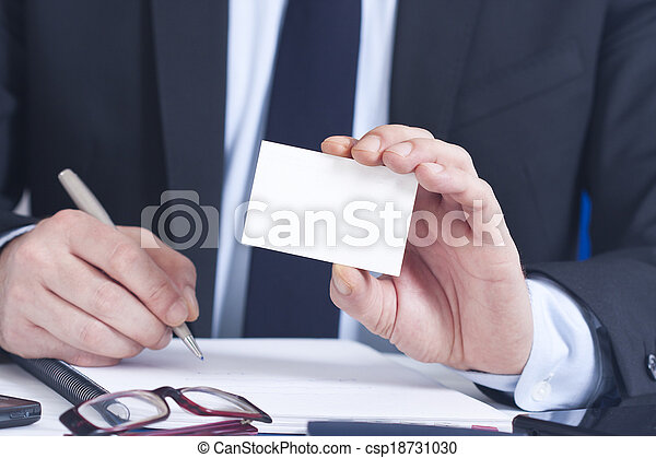 businessman with business card in foreground  - csp18731030