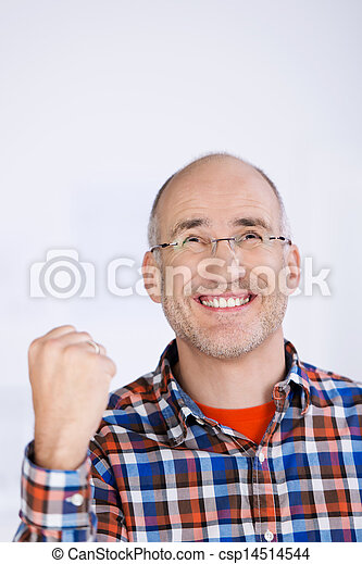 Businessman With Clenched Fist Looking Up In Office - csp14514544