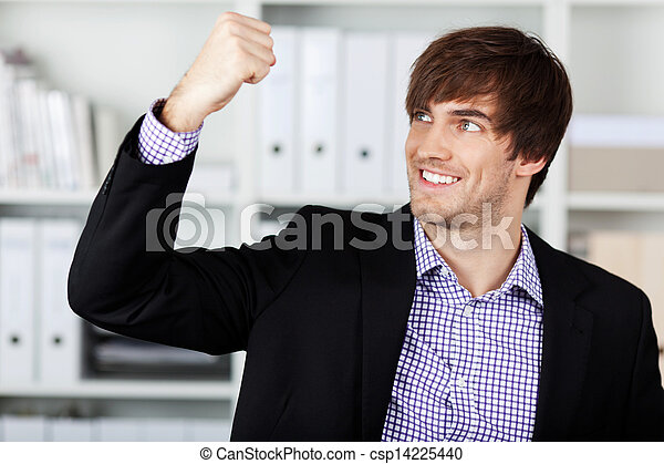 Businessman With Clenched Fist Celebrating Victory In Office - csp14225440