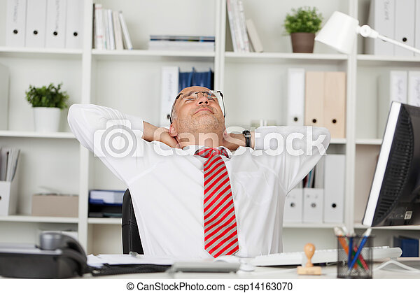 Businessman With Hands Behind Head At Desk - csp14163070
