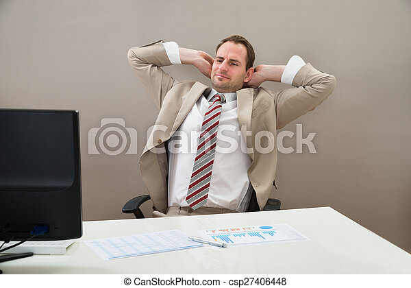 Businessman With Hands Behind Head In Office - csp27406448