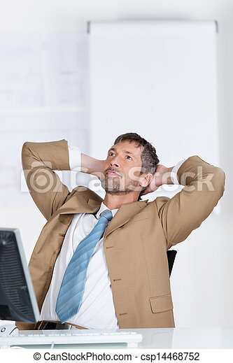 Businessman With Hands Behind Head Looking Up At Desk - csp14468752