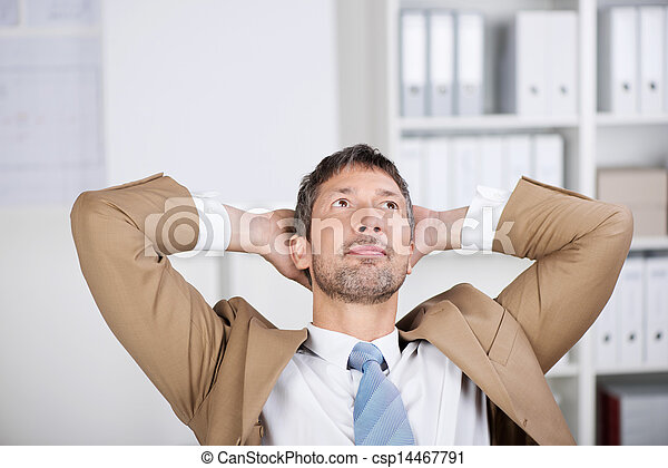 Businessman With Hands Behind Head Looking Up In Office - csp14467791