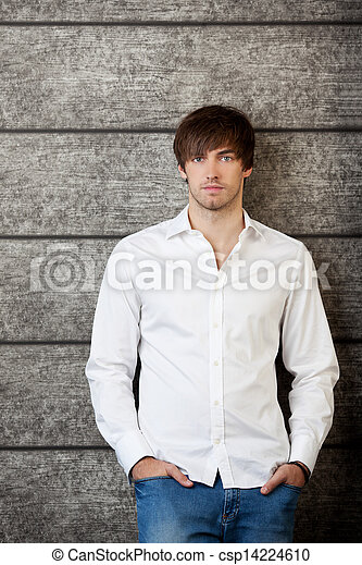 Businessman With Hands In Pockets Standing Against Wooden Wall - csp14224610