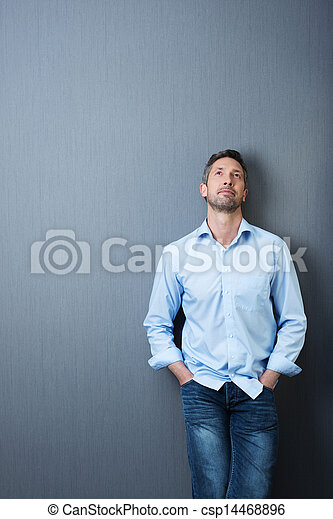 Businessman With Hands In Pockets Looking Up Against Blue Wall - csp14468896