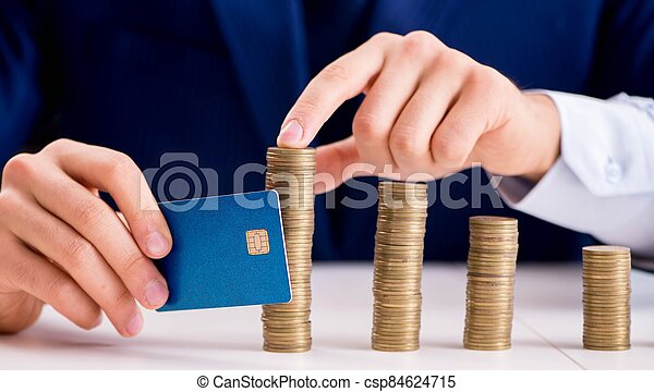 Businessman with stacks of coins in the office - csp84624715