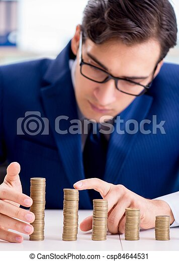 Businessman with stacks of coins in the office - csp84644531