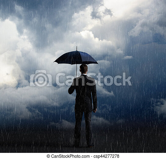 Businessman with umbrella standing over stormy background. Business, protection, crisis concept. - csp44277278