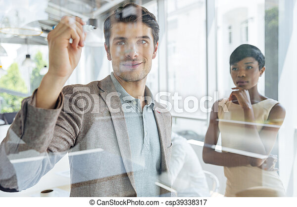 Businessman working with businesswoman and writing on transparent board - csp39338317