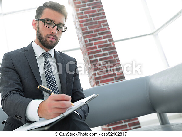 Businessman writing in a notebook in an office - csp52462817
