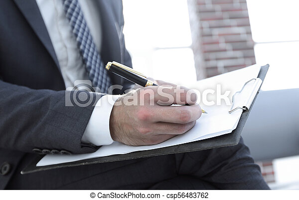 Businessman writing in a notebook in an office - csp56483762