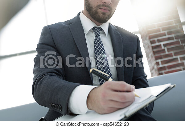 Businessman writing in a notebook in an office - csp54652120