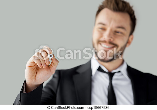 Businessman writing on transparent wipe board. Cheerful young man in formalwear writing something on transparent wipe board while standing against grey background - csp18667836