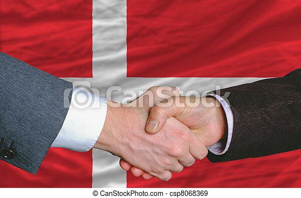 businessmen handshake after good deal in front of denmark flag - csp8068369