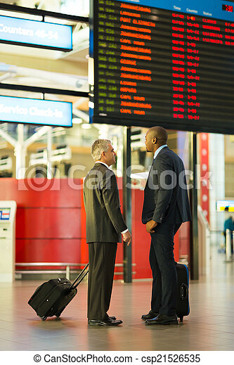 businessmen in front of airport information board - csp21526535
