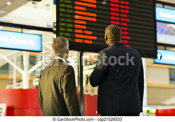 businessmen looking at flight information board - csp21526533