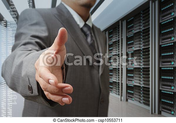 businessmen offer hand shake in a technology data center - csp10553711