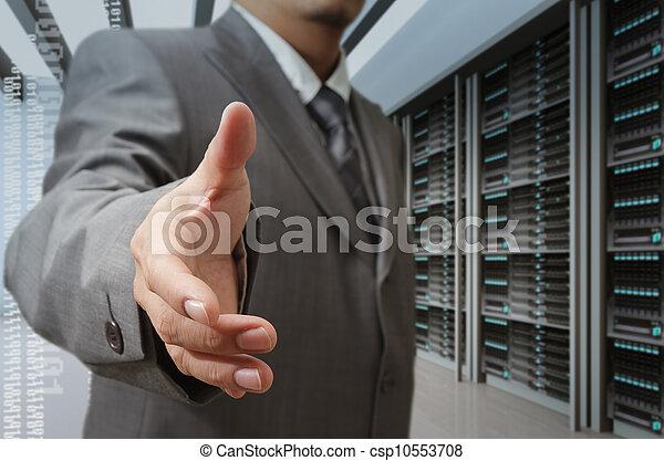 businessmen offer hand shake in a technology data center - csp10553708