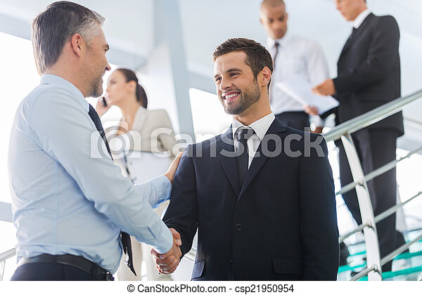 Businessmen shaking hands. Two confident businessmen shaking hands and smiling while standing at the staircase together with people in the background - csp21950954