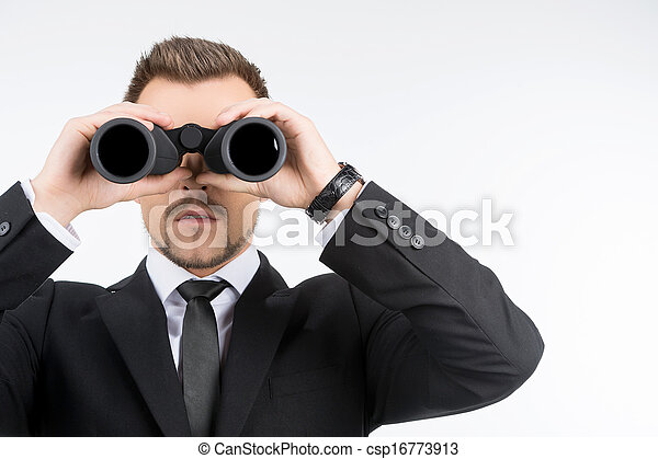 Businessmen with binoculars. Young businessmen looking through the binoculars while isolated on white - csp16773913