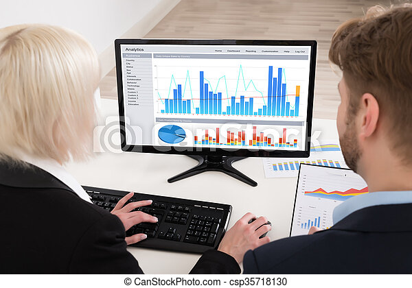 Businesspeople Analyzing Graph On Computer - csp35718130