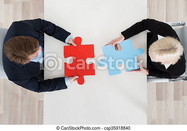 Businesspeople Connecting Puzzle Pieces - csp35918840