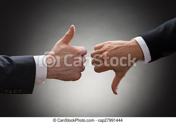 Businesspeople Hands Showing Thumb Up And Thumb Down - csp27991444