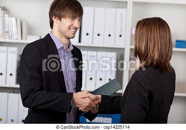 Businesspeople Shaking Hands In Office - csp14225114
