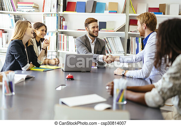 Businesspeople shaking hands in office - csp30814007