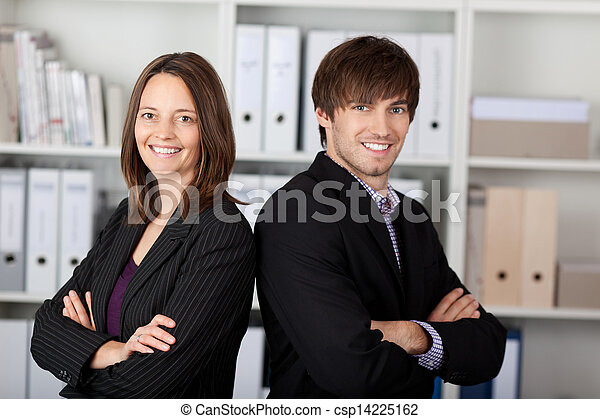 Businesspeople With Arms Crossed Standing In Office - csp14225162
