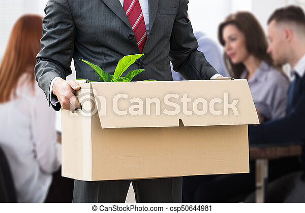 Businessperson Holding Belongings In Cardboard Box - csp50644981