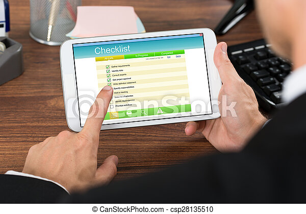Businessperson Holding Mobile Phone With Checklist - csp28135510