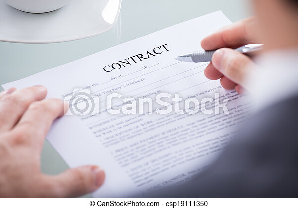 Businessperson Holding Pen On A Document - csp19111350