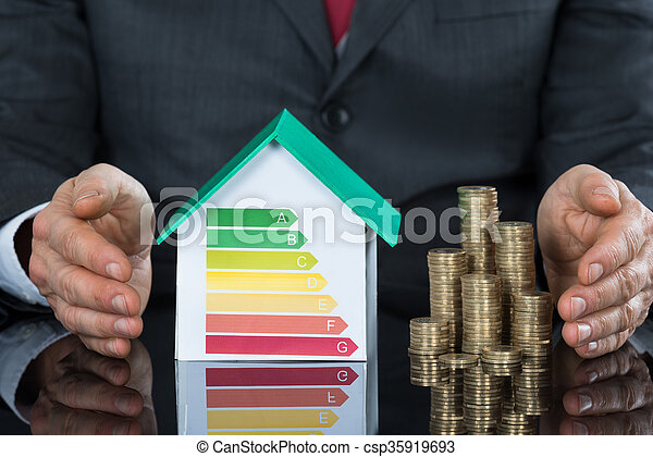 Businessperson Protecting House Model Stack Of Coins - csp35919693