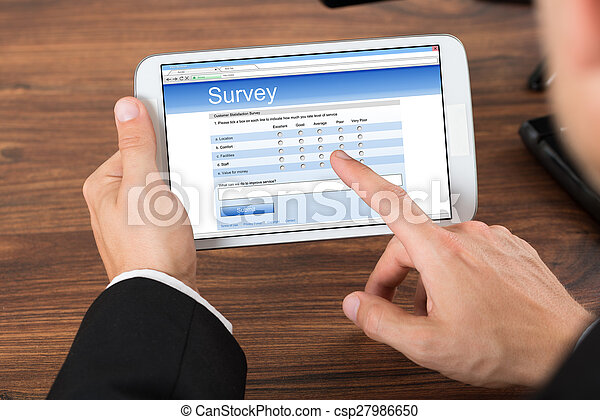 Businessperson With Mobile Phone Showing Survey Form - csp27986650