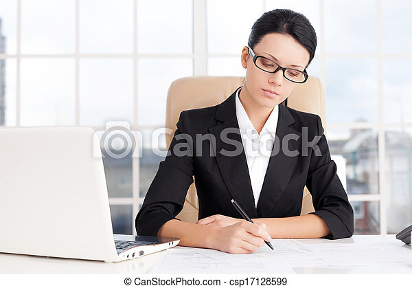 Businesswoman at work. Confident young business writing something on paper while sitting at her working place - csp17128599