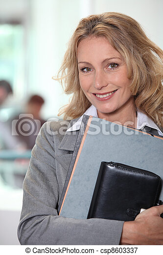 Businesswoman carrying files and an agenda - csp8603337