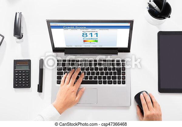Businesswoman Checking Credit Score On Laptop - csp47366468
