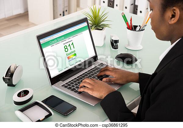 Businesswoman Checking Credit Score On Laptop - csp36861295