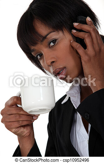 Businesswoman drinking coffee during call - csp10952496