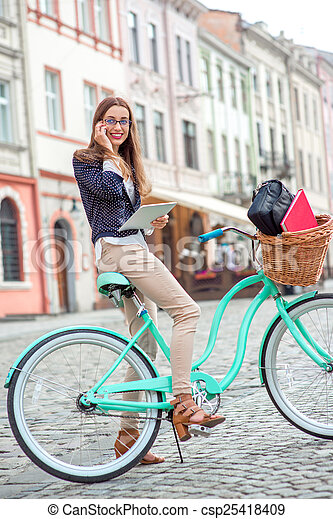 Businesswoman going to work by bicycle speaking phone in old city center background - csp25418409