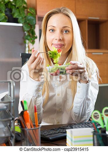 Businesswoman having lunch in office - csp23915415