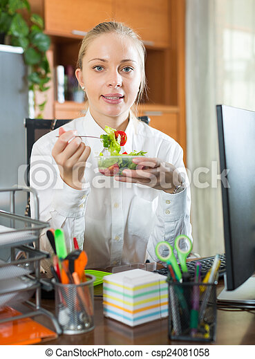 Businesswoman having lunch in office - csp24081058