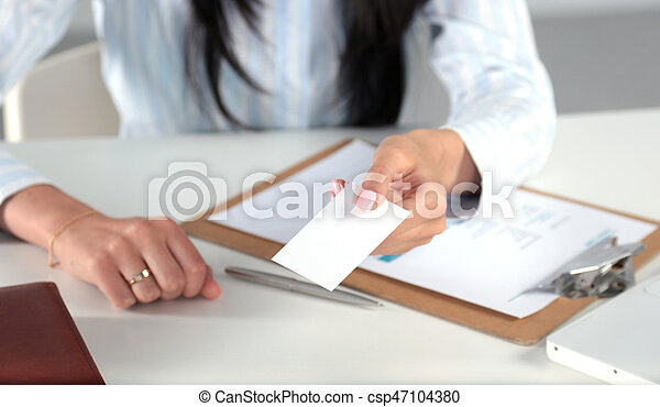 Businesswoman holding blank visit card ,sitting on the desk - csp47104380