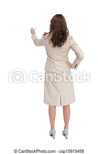Businesswoman holding business card standing back to camera - csp15915458